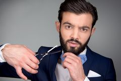 Gut aussehender Mann mit Bart unter Verwendung der Scheren Stockfoto