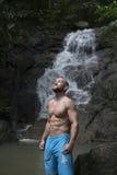 Gut aussehender Mann mit dem Bart, der die blauen kurzen Hosen oben stehen und schauen nahe Wasserfall trägt Stockfotografie