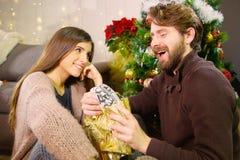 Gut aussehender Mann mit dem Bart, der Weihnachtsgeschenk von der Freundin empfängt lizenzfreie stockfotografie