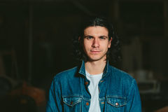 Gut aussehender Mann mit langem Haar Brunette in einer Denimjacke Stockfotografie