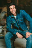 Gut aussehender Mann mit langem Haar Brunette in einer Denimjacke Stockfoto
