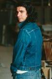 Gut aussehender Mann mit langem Haar Brunette in einer Denimjacke Lizenzfreies Stockfoto