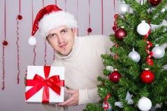 Gut aussehender Mann in Sankt-Hut mit Geschenkbox und verziertem Weihnachten Stockbilder