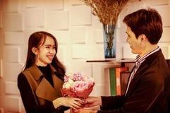 Gut aussehender Mann schickt ein Lächeln zum Glückwunschblumenstrauß von Rosen, geben einem Mädchen einen glücklichen Liebhaber,  lizenzfreies stockfoto