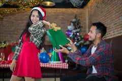 Gut aussehender Mann schickte der Schönheit grüne Geschenktasche, das rotes Kleid und Weihnachtsmann-Hut an der Partei tragen Lizenzfreie Stockfotos