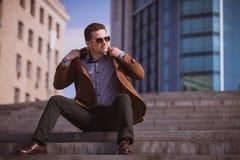 Gut aussehender Mann sitzt auf einem Wolkenkratzerhintergrund lizenzfreie stockfotos