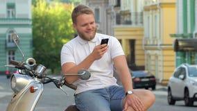 Gut aussehender Mann sitzt auf Roller stock footage