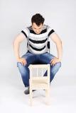 Gut aussehender Mann sitzt auf Stuhl und betrachtet kleinen Stuhl Stockfotografie