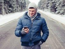 Gut aussehender Mann steht auf einer schneebedeckten Straße und schaut in seinem Handy stockfoto