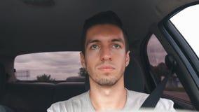 Gut aussehender Mann täuscht herum zu der Zeit des Fahrens