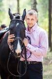 Gut aussehender Mann und Pferd Stockbilder