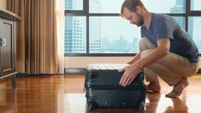 Gut aussehender Mann verpackt einen Koffer in einem Raum mit einem panoramischen Fenster, das die Wolkenkratzer übersieht stock footage