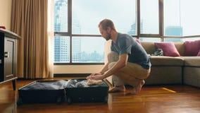Gut aussehender Mann verpackt einen Koffer in einem Raum mit einem panoramischen Fenster, das die Wolkenkratzer übersieht stock video footage