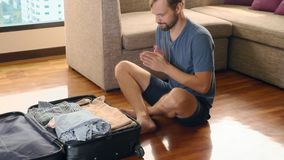 Gut aussehender Mann verpackt einen Koffer in einem Raum mit einem panoramischen Fenster, das die Wolkenkratzer übersieht stock video