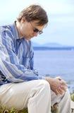 Gut aussehender Mann in Vierziger betend durch Seite von See Lizenzfreie Stockbilder