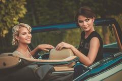 Gut gekleidet Damen in einem klassischen Kabriolett lizenzfreie stockfotos