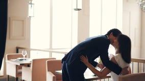 Gut gekleidet Kerl holt seiner glücklichen Freundin im Restaurant Blumen und küsst sie dann bei Tisch sitzend und stock video
