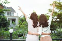 Gut gekleidet Lächeln der glücklichen jungen Freundinnen bei der Stellung zu Lizenzfreie Stockfotografie