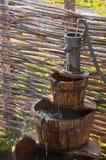 Gut mit manueller Wasserpumpe und -behältern unten Stockfotografie