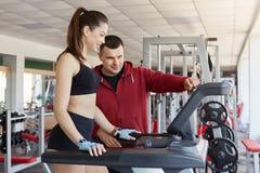 Gut qualifizierter Trainer erklärt seinem Kunden, wie man Tretmühle, tragendes schwarzes T-Shirt und rote Sportjacke benutzt Sc stockfotografie