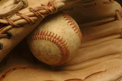 Gut-verwendeter Baseball nestled in einem Handschuh. Stockfoto