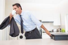 Gut zurechtgemachter trinkender Kaffee des Mannes beim Halten des Aktenkoffers in der Küche Stockfoto