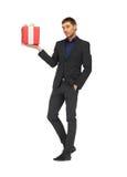 gutaussehender Mann in der Klage mit einer Geschenkbox Lizenzfreie Stockfotos