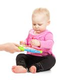 Gute baby in jacket and black trousers draws Stock Photos