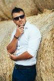 Gute Blicke des jungen Mannes in der Sonnenbrille am Stroh Stockbilder