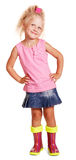 Gute little blond girl in blouse, skirt, rubber boots isolated. royalty free stock image