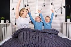 Guten Morgen! Mutter und zwei junge Söhne dehnen in Bett aus Positives Wecken stockbild
