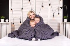 Guten Morgen! Mutter und zwei kleine Söhne verstecken sich unter einer gestrickten Decke Positives Wecken lizenzfreies stockbild