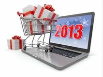 Guten Rutsch ins Neue Jahr 2013. Laptop und Geschenke auf Einkaufswagen. Stockfotografie