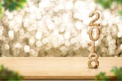 Guten Rutsch ins Neue Jahr 2018 auf hölzernem Tabellen- und Unschärfe Weihnachtsbaum foregr