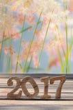 Guten Rutsch ins Neue Jahr 2017 auf hölzerner Planke und Unschärfe bedeckt Blumenhintergrund mit Gras Lizenzfreies Stockfoto