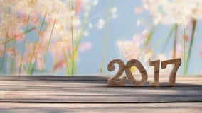 Guten Rutsch ins Neue Jahr 2017 auf hölzerner Planke und Unschärfe bedeckt Blumenhintergrund mit Gras Lizenzfreie Stockfotografie