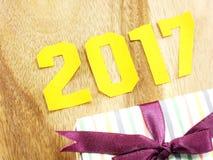 Guten Rutsch ins Neue Jahr-Beschriftung mit dem Geschenk auf hölzernem Hintergrund Stockfoto