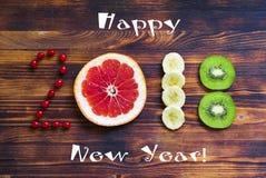 Guten Rutsch ins Neue Jahr 2018 der Frucht und der Beeren auf hölzernem Hintergrund Stockbilder