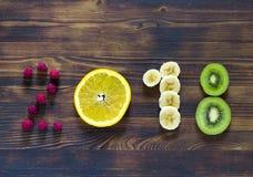Guten Rutsch ins Neue Jahr 2018 der Frucht und der Beeren auf hölzernem Hintergrund lizenzfreies stockbild