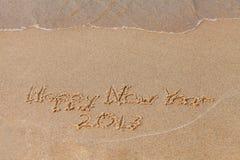 Guten Rutsch ins Neue Jahr 2017 - die Aufschrift auf dem Sandstrand mit einer weichen Welle Stockfoto