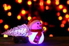 Guten Rutsch ins Neue Jahr 2017 färbt Schneemann- und Weihnachtsbaum auf bokeh Hintergrund Lizenzfreie Stockfotos