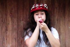 Guten Rutsch ins Neue Jahr-Feier mit Schlaggeräuschherstellern des hübschen Mädchens, Parteigebläse an der Partei auf hölzernem H lizenzfreie stockfotografie