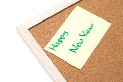 Guten Rutsch ins Neue Jahr geschrieben auf gelbes Blatt, Korkenbrett Stockfotos