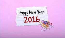 Guten Rutsch ins Neue Jahr 2016 geschrieben auf Papier mit rosa Hintergrund Stockfotografie