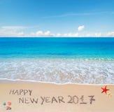 Guten Rutsch ins Neue Jahr 2017 geschrieben in den Sand Lizenzfreie Stockfotos