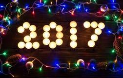 Guten Rutsch ins Neue Jahr 2017 geschrieben mit brennenden Kerzen Lizenzfreies Stockbild
