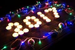 Guten Rutsch ins Neue Jahr 2017 geschrieben mit brennenden Kerzen Stockfotografie