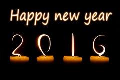 Guten Rutsch ins Neue Jahr 2016 geschrieben mit Kerzenflammen Lizenzfreie Stockfotos