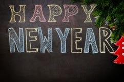 Guten Rutsch ins Neue Jahr geschrieben mit Kreide auf einen schwarzen Hintergrund Lizenzfreie Stockbilder