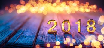 2018 - Guten Rutsch ins Neue Jahr - goldene Zahlen auf Defocused Tabelle stockfotografie